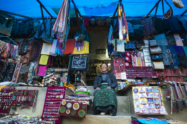 Central region, Nepal - November 13, 2012: A Tibetan woman sitting outside her shop in Namche Bazaar
