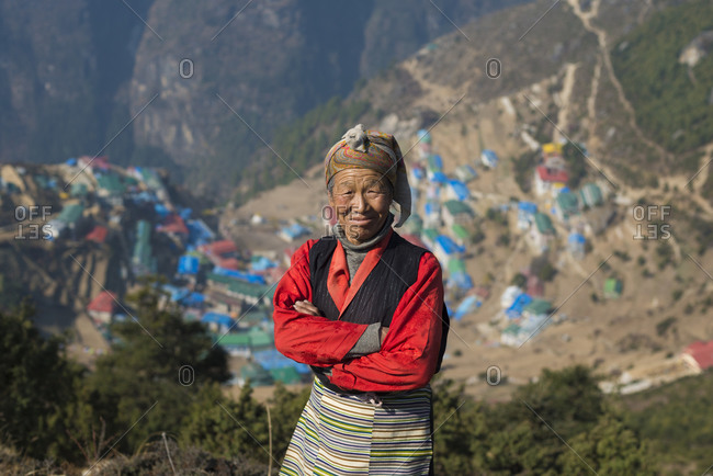 A Tibetan woman wearing traditional dress in the Everest region of Nepal with Namche Bazaar visible in the distance