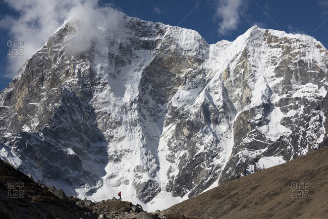 A trekker makes her way up the Khumbu valley towards Everest base camp with huge mass of Cholatse behind