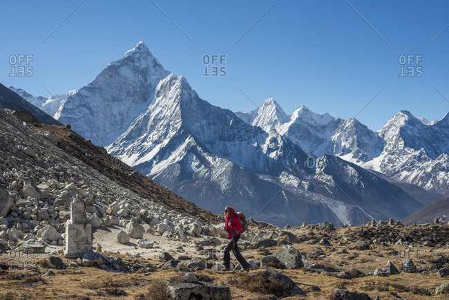 A trekker makes her way up the Khumbu valley towards Everest base camp with the pyramidal peak of Ama Dablam in the distance
