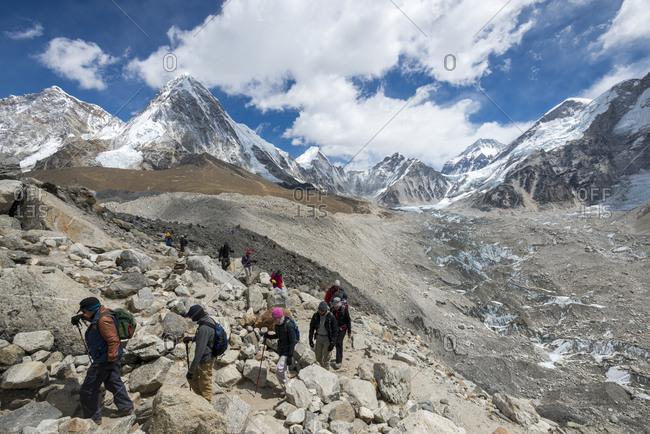 Dingboche, Khumbu, Everest region, Nepal - April 19, 2013: Trekkers make their way down from Everest Base Camp beside the Khumbu glacier in Nepal