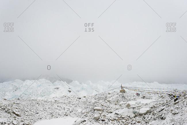 Trekkers on the Khumbu glacier pass a chorten adorned with prayer flags near Everest Base Camp.