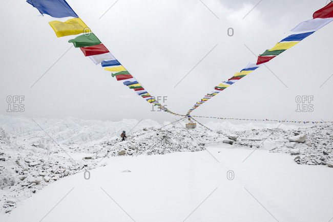 A porter walks past a Puja tied with prayer flags at Everest Base Camp carrying supplies for a climbing expedition in Nepal