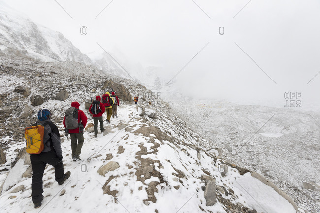 Dingboche, Khumbu, Nepal - April 21, 2013: Trekkers walking in to Everest base camp which can be seen as a cluster of tents in the distance on the Khumbu glacier