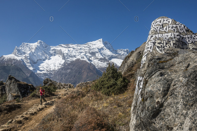 Trekking in the Everest region of Nepal with views of Kongde peak in the distance