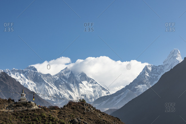 Trekkers pass a stupa on their was to Everest Base Camp in the Khumbu region on Nepal with views of Ama Dablam in the distance