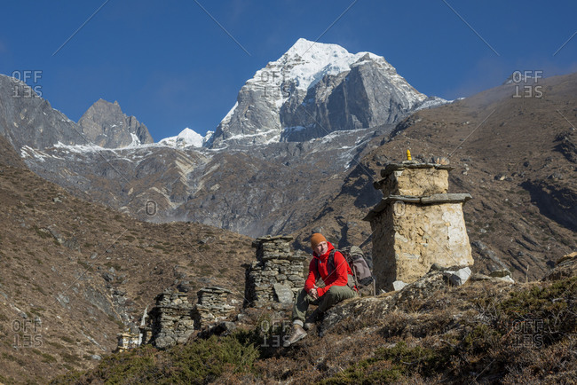 A hiker on the trail to Everest Base Camp sits beside a row of chortens