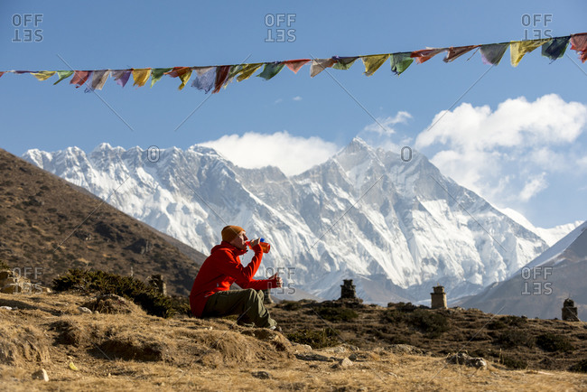 A hiker on the trail to Everest Base Camp sits down under a string of prayer flags to take a break and also take in the views.