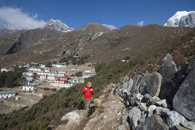 In the Khumbu valley in the Everest region of Nepal a hiker walks past a wall of Mani stones which are inscribed with an ancient Tibetan mantra with a view of old Pangboche in the distance