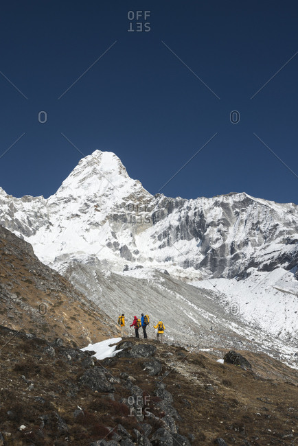 A team of climbers gaze up at the prospect ahead, Ama Dablam in the Everest region of Nepal