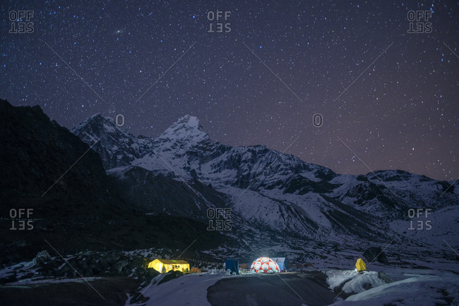 Ama Dablam base camp in the Everest region of Nepal glows under stars with the peak of Ama Dablam also visible in the moonlight