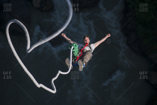A man smiles for the camera while bouncing back on a bungee jump at The Last Resort in Nepal
