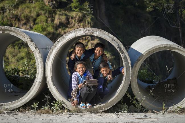 Kodari, Nepal - November 14, 2013: Children in Nepal playing inside concrete construction pipes