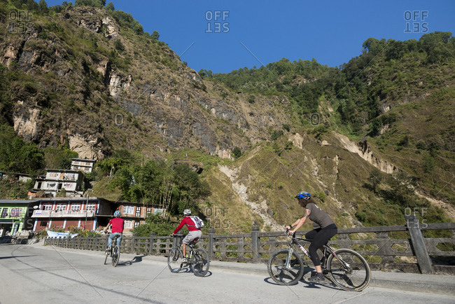 Kodari, Nepal - November 14, 2013: Mountain biking through a small village near the Tibetan border in Nepal