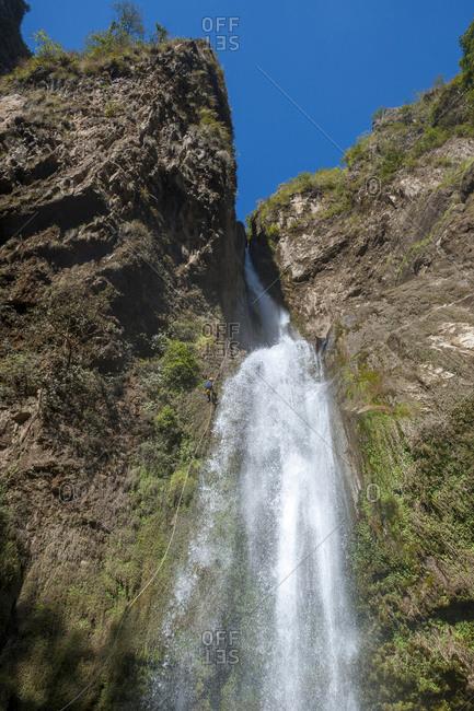 A man abseils down a waterfall in Nepal near the Tibetan border