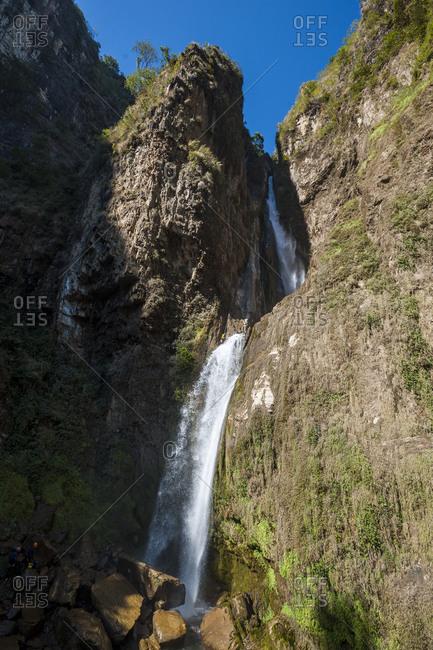 A man abseils down a 100m waterfall in Nepal near the Tibetan border
