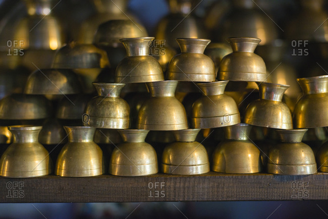 Typical Nepalese brass cups stacked up on a shelf in Bandipur