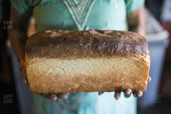 A woman holds up a freshly baked loaf of bread from an oven in a traditional house in Bandipur, a small village in central Nepal