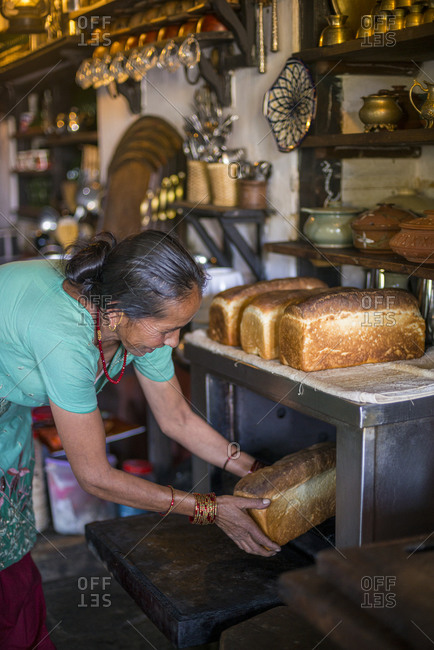 A woman removes freshly baked bread from an oven in a traditional house in Bandipur, a small village in central Nepal