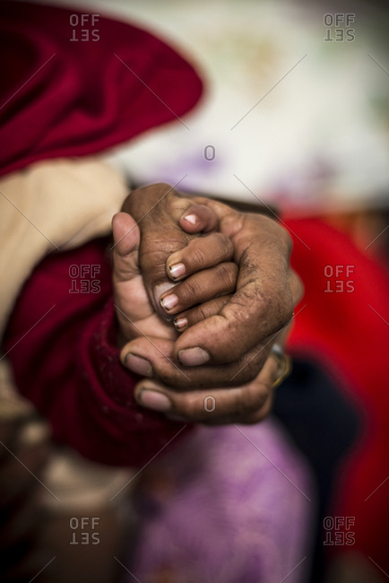 A mother holds her baby's hand in a rural hospital
