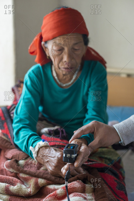 A doctor attaches an oximeter to a patients finger to check oxygen and pulse in a rural hospital in Nepal