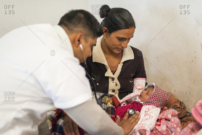 A general practitioner checks a patient's baby with a stethoscope in a rural hospital in Nepal