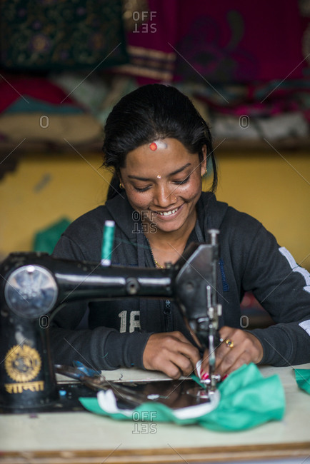 A woman works on a sewing machine in a village in Nepal