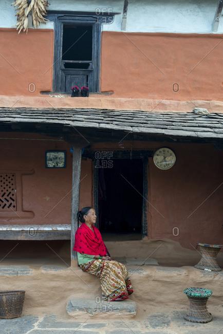 Myagdi, Beni district, Nepal - November 27, 2013: Elderly woman sitting outside her house