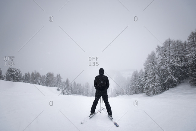 A skier in the resort of Vigo Di Fassa in the Dolomites in Italy stops at the top of the piste to consider the way down