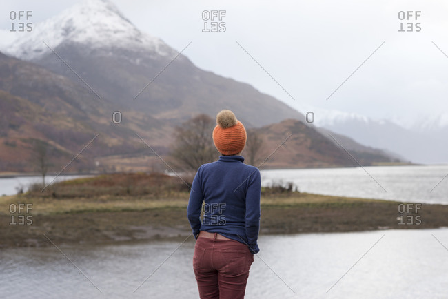 A woman looks out across Loch Leven on a misty day in Scotland