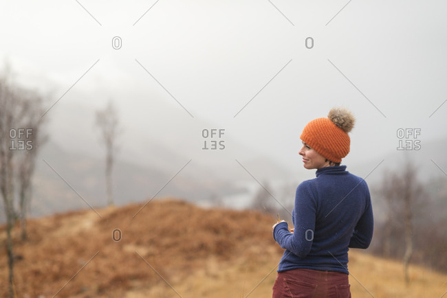 A woman walking above Loch Leven on a misty day in Scotland stops to admire the view