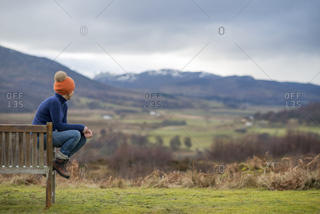 A woman walking in the Cairngorms national park in Scotland sits on a bench to admire the view
