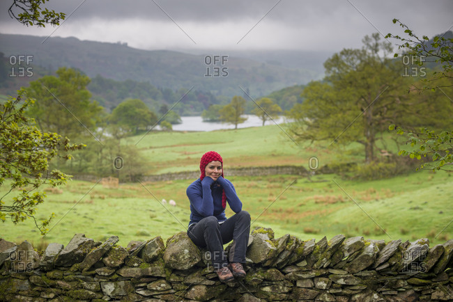 A woman rests on a dry stone wall while on holiday in The Lake District with views of Rydal water in the distance