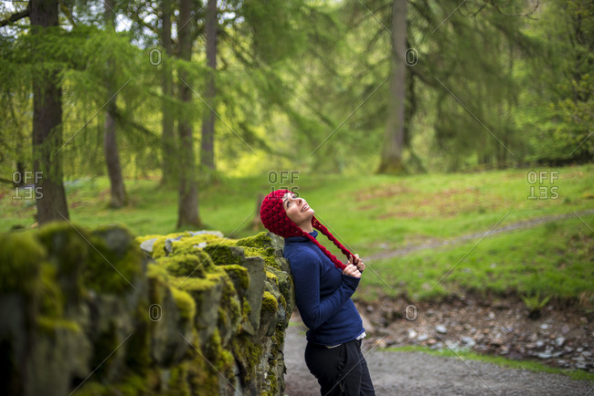 A woman rests against a wall while walking near Rydal Water in The Lake District