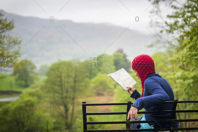 A woman checks her map while walking near Grasmere in The Lake District