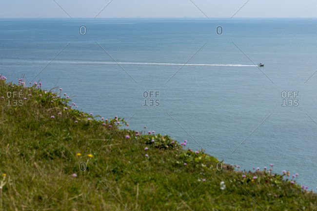 A speedboat leaves a long white trail in its wake seen from the clifftops at Beachy Head