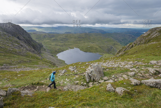 Walking in the Great Langdale valley in The Lake District with a view of Stickle Tarn in the distance