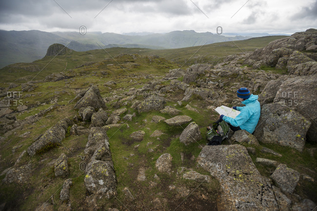 A woman checks her map in the Great Langdale valley with a view of Stickle Pike in the distance in The Lake District