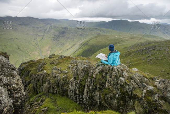 A woman sits to check her map while looking towards Great Langdale valley from the Langdale Pikes in The Lake District