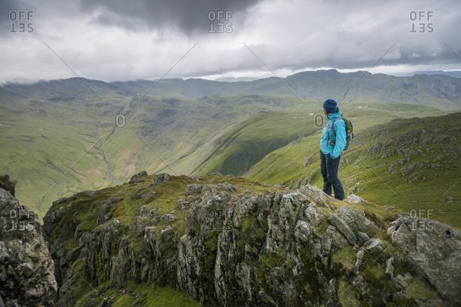 A woman looks towards Great Langdale valley from the Langdale Pikes in The Lake District