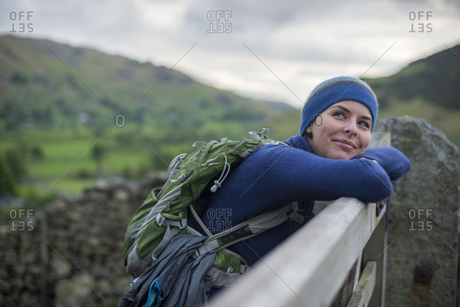 A woman rests on a gate in the Great Langdale valley in The Lake District