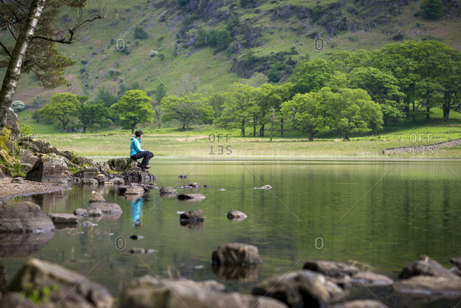 A woman sits beside Blea Tarn in the Great Langdale valley