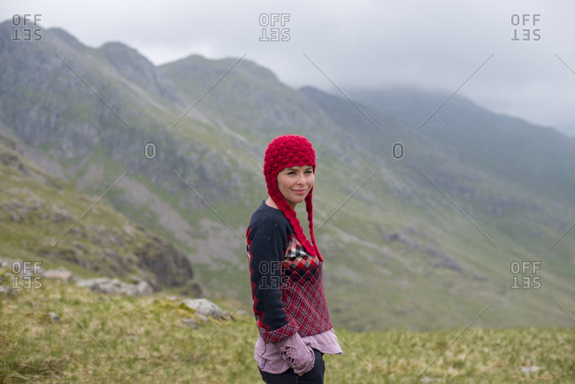 A woman in the Great Langdale valley with views of Crinkle Crags in the distance