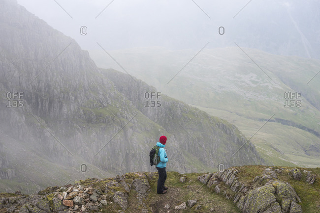 A woman looks towards Great Langdale from Crinkle Crags in The Lake District