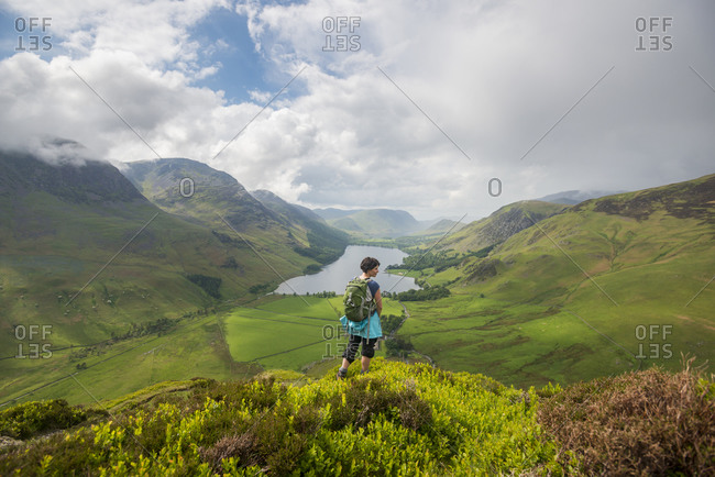 A woman looks out over Buttermere from the Fleetwith Pike in in The Lake District
