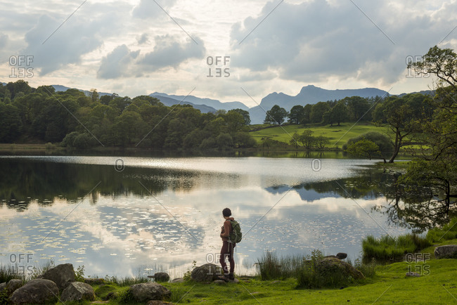 A woman looks out over Loughrigg Tarn near Ambleside in The Lake District