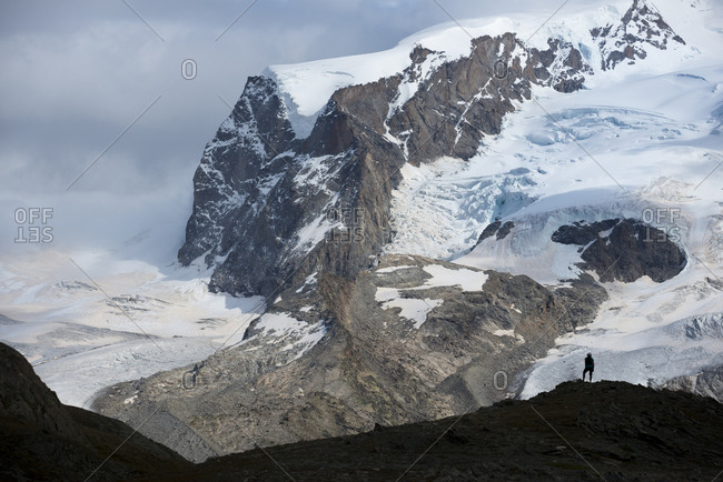 Trekking on the trail beside the Gorner Glacier with a view of Monte Rosa in the distance