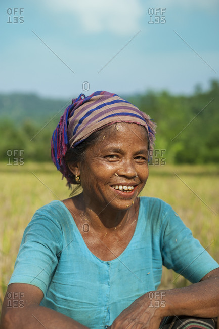 A woman in the Chittangong Hill Tracts stops work in a rice paddie for a moment