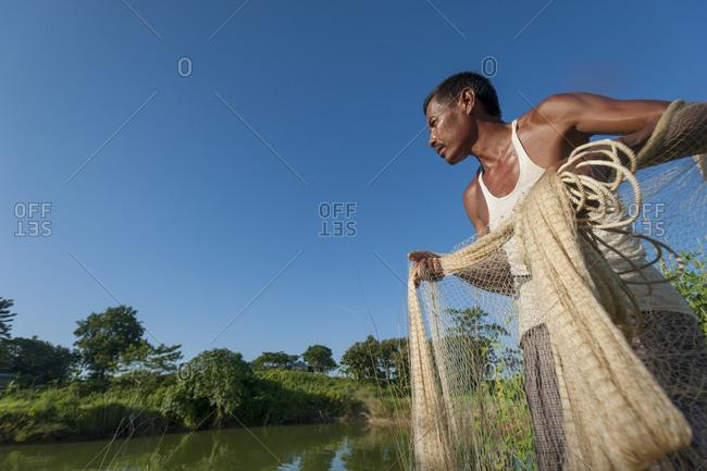 A man prepares to cast his net into the river near Khagracharri