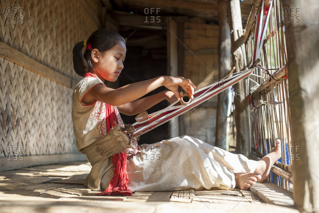 A girl learns the traditional art of weaving on a hand loom